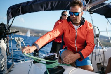 Handsome strong man sailing with his friends on boat