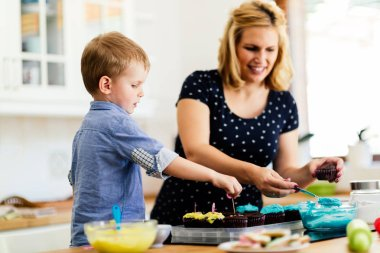 Child helping mother prepare muffins in kitchen