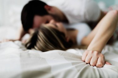 Young attractive happy couple having romantic time in bed
