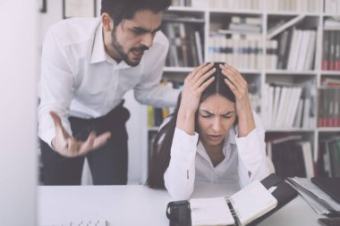 Businessman yelling at female colleague at desk in office
