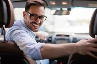 Portrait of a handsome young businessman driving car