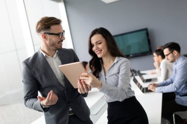 Happy business colleagues in modern office using tablet