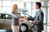 Successful happy businessman in a car dealership - sale of vehicles to customers