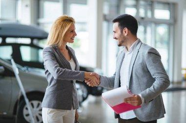 Handsome young salesman at car dealership selling vehichles