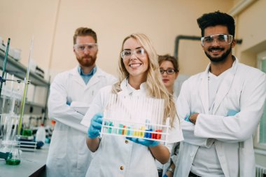 Group of young successful scientists posing for camera in laboratory