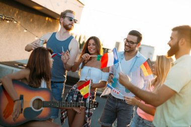 Group of people holding national flags and having fun on rooftop