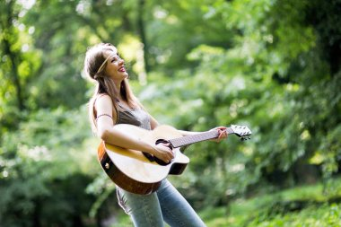 Beautiful woman playing acoustic guitar in nature