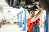 Auto mechanik mění motorový olej v motoru v Údržba opravy čerpací stanici