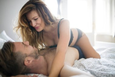 Beautiful couple in love being passionate in bed