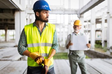Engineer and construction site manager working with blueprints and plans stock vector