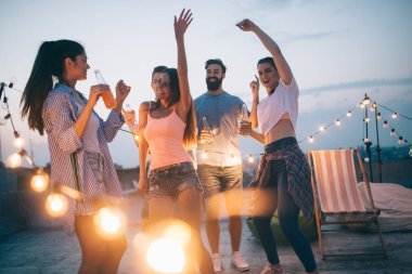 Happy friends having party on top of the roof . Fun, summer, city lifestyle and friendship concept