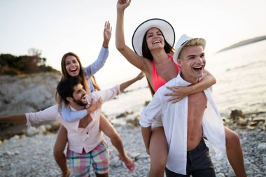 Cheerful couples friends enjoying weekend and having fun on beach