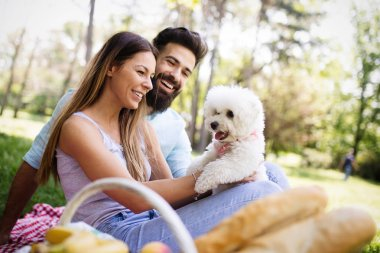 Lifestyle, happy family resting at a picnic in the park with a dog