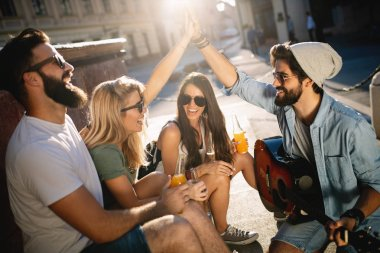 Group of friends enjoying a summer day outdoor playing guitar. Happy young people having fun spending good time together