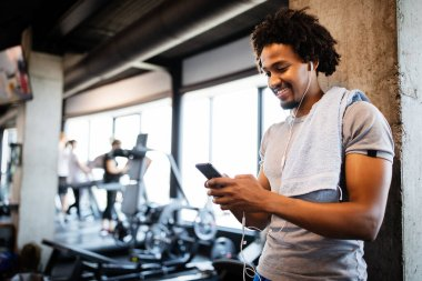 Young fit handsome man using phone while having exercise break in gym
