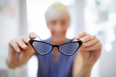 Pretty senior woman is choosing new glasses at optics store stock vector