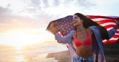 Cheerful excited woman outdoors on the beach holding USA flag having fun. stock vector
