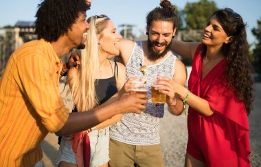 Group of happy young friends hanging out and enjoying drinks, festival