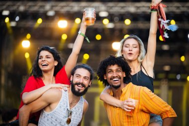 Group of young happy people enjoying outdoor music festival