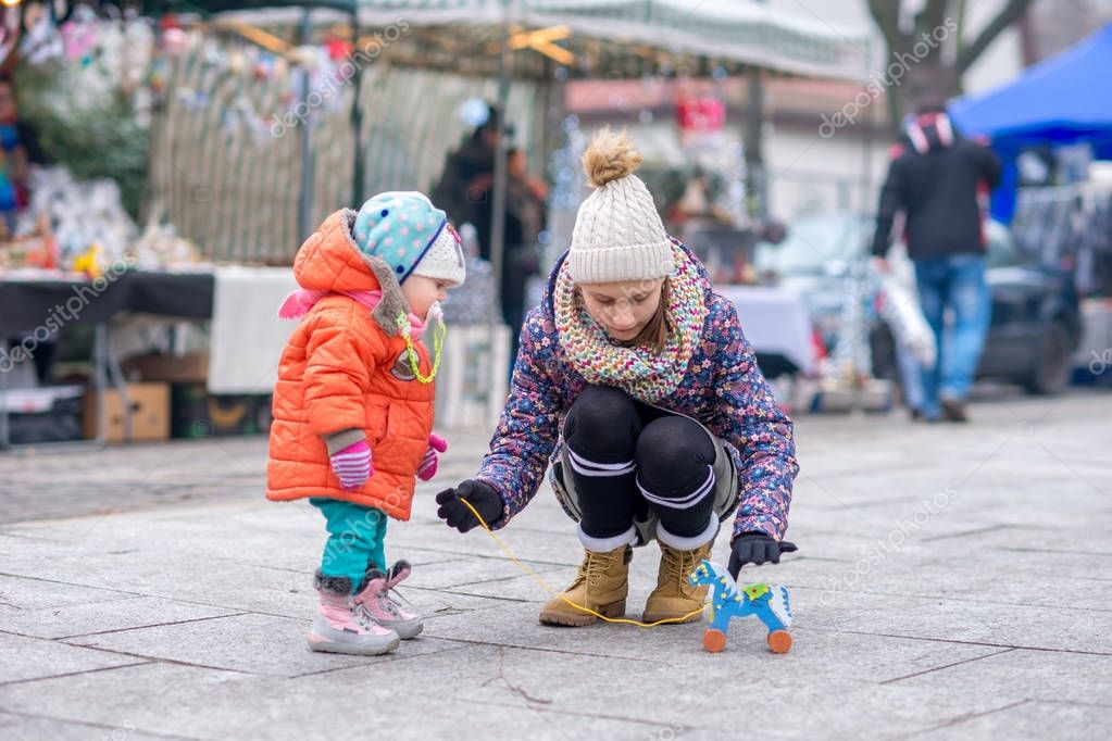 The kid and his older sister play with a wooden horse in cold weather on the street.