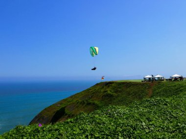 Scenic view of paraglider flying on the coast of Miraflores touristic district of Lima. As a background there is the Lima cliff, the Pacific Ocean and the horizon over water on a day with blue sky. Paragliding is a popular sport on the coast