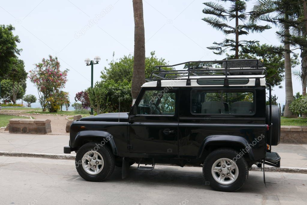 Lima, Peru. December 27, 2017. Front and side view of a mint condition black Land Rover Defender with white top. The car is parked in a street of Barranco district of Lima along side a public park.