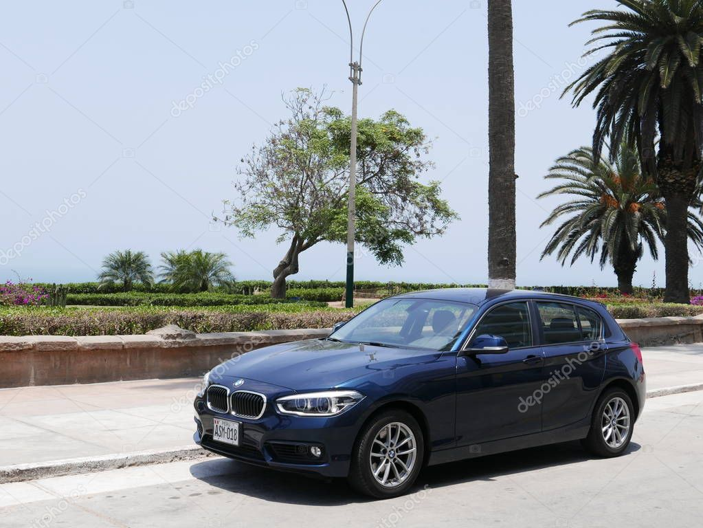 Lima, Peru. October 12, 2017. Front and side view of a blue mint condition BMW 120i four doors German car parked in Barranco district of Lima. In the background there is a park with flowers, plants and trees at coastline