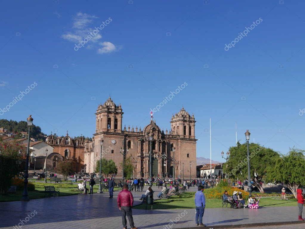 Main square of Cusco or the Plaza de Armas with its ornamental gardens and the Cathedral, lampposts, blue sky, incidental people, plants and trees. Cusco is the most visited city in Peru and an UNESCO World Heritage Site