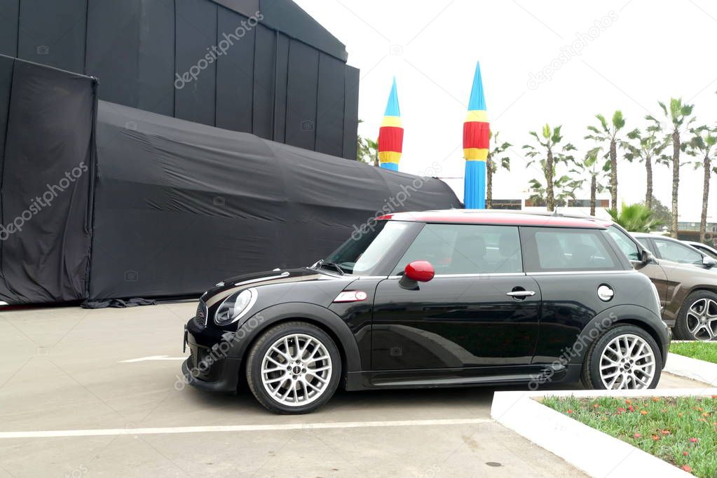 Lima, Peru. August 19, 2018. Skill condition black and red Mini Cooper S John Cooper Works parked in Chorrillos district of Lima. In the image there are also the headlights, the grille, aluminium wheels, a rearview mirror, a turn signal and nature