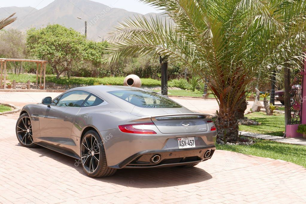 Lima, Peru. November 11, 2017. Rear and side view of a mint condition gray Aston Martin Vanquish coupe at south of Lima. This car was produced between 2001 and 2007 in the UK. Garden, palms, lawn, plants and mountains are in the image