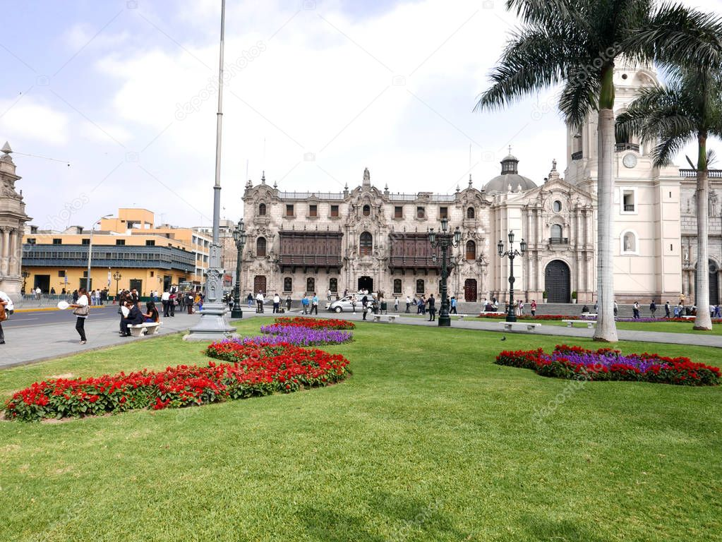 View of the Archbishopric palace with its historic and colonial balconies, part of the Cathedral and ornamental garden of the main square in the historic center of Lima, an UNESCO World Heritage Site.