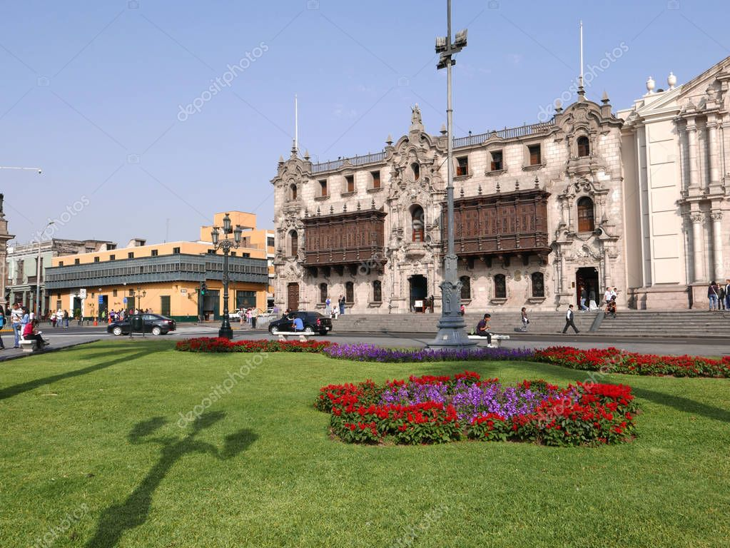 View of the Archbishopric palace with its historic and colonial balconies, a yellow ancient mansion with very big green wooden balcony and ornamental garden of the main square in the historic center of Lima, an UNESCO World Heritage Site.