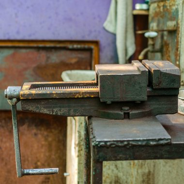 Old metal manual vise tool, in the home workshop on workbench. Vice is tool for industrial works. Selective focus. For instagram format. Square. Close-up.