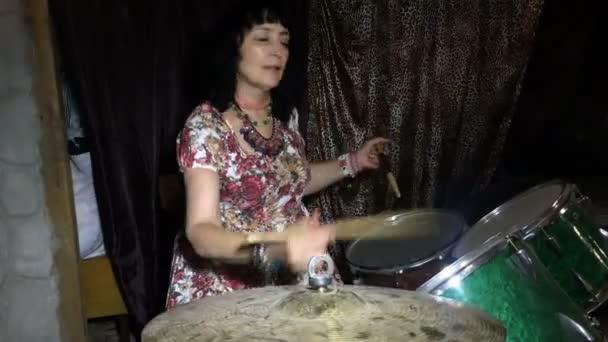 Erwachsene Frau hat Spaß, lernt, auf einem alten Vintage-Schlagzeug in einer Garage oder im Keller zu spielen.