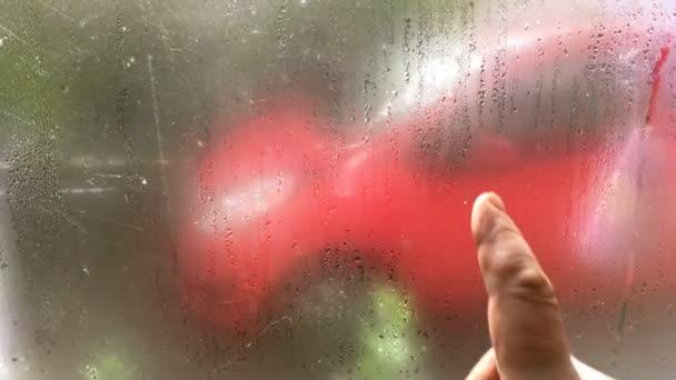 Tvar srdce ruka kreslí lásku na chladné kondenzace okno s čůrky. Koncepce designu pro lásku nebo romantické