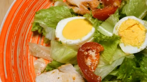 Caesar salad in red plate. Caesar salad consists of roasted chicken breast, iceberg lettuce, tomato, parmesan cheese. Popular dish of European cuisine and cuisines of other countries of world.