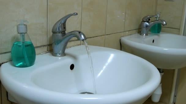 Čistá voda teče z dirty kohoutku. Tekoucí vodou. Představující plýtvání vodou. Barevné záblesky blikání.