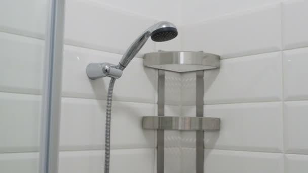 Interiér je moderní koupelna. Prázdné sprchovým koutem s bílou dlažbu stěny a police. Pohled z vrcholu dolů.