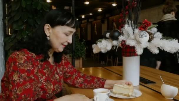 Üzletasszony iszik kávé és megeszi tortát egy kávézó vagy étterem, és jegyzeteket írja papírra.