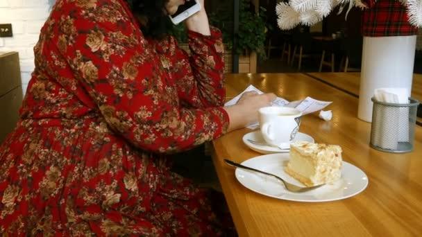 Pije kávu a jí dort v kavárně nebo v restauraci a píše poznámky na papír.