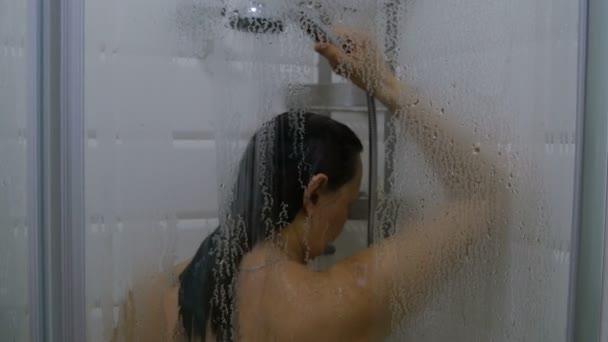 Fürdőszoba interior. Felnőtt nő kaukázusi etnikai átveszi egy zuhany kabin párás üveg. Modern fürdőszoba.