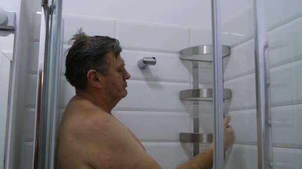 Interiér koupelny. Dospělých, Kavkazský národnost člověka, bere sprchu a předstírá, že udělat selfie s Sprchová hlavice. Moderní sprchový kout šplouchání vody v koupelně