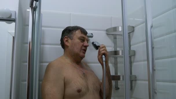 Interiér koupelny. Dospělých, Kavkazský národnost člověka, bere sprchu a předstírá, že mluví do telefonu. Moderní sprchový kout šplouchání vody v koupelně.