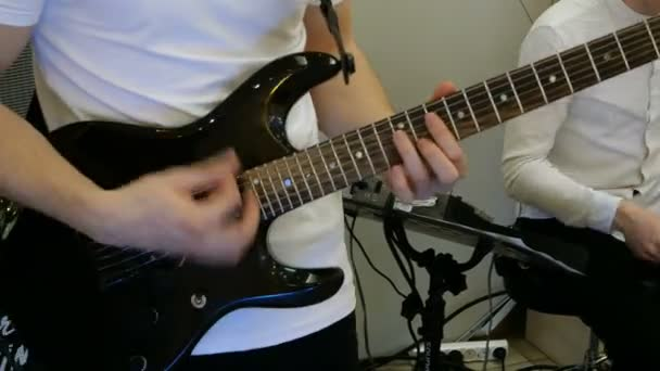 Hands of guitarist from musical or rock band, which play electric guitar indoors.