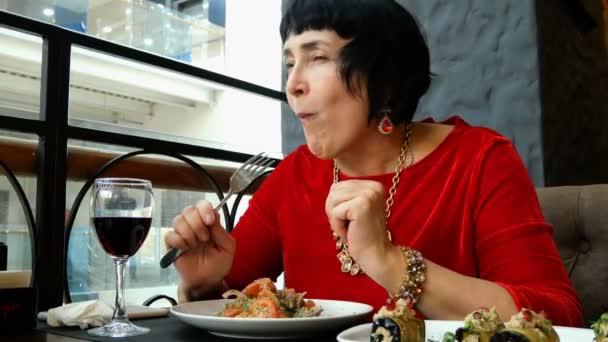 Elegantní starší žena v restauraci či kavárně je jíst salát a pití vína.