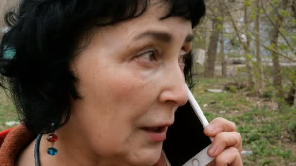 Adult elegant brunette woman emotionally talking on her smartphone outdoors.
