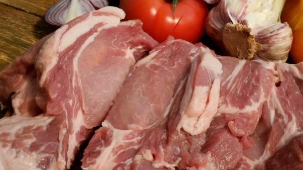 Steaky ze syrového masa jsou nakrájen z velkého kusu vepřového nebo hovězího masa na dřevěné řezací desce. Zelenina: rajčata, sladká paprika, česnek. Close-up.