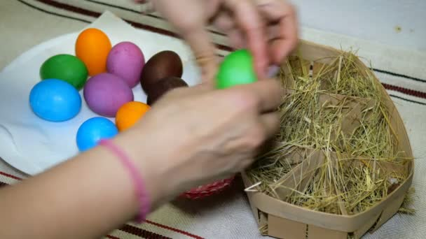 Homemade preparation for the holiday Easter. Woman puts colorful Easter eggs in basket with hay.