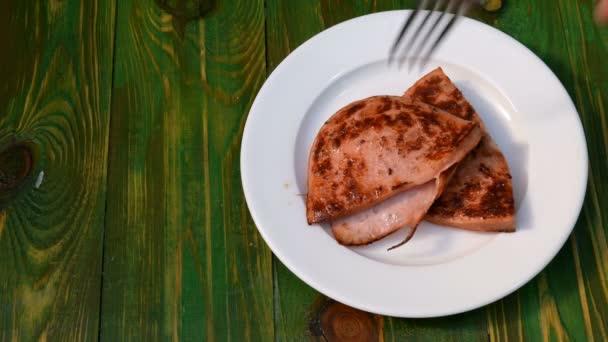 Domácí Rychlá kuchyně. Smažené klobásy jsou položené na talíř, stejně jako kečup a nakrájené pečivo. Koncept vaření rychle levných jídel. Na zeleném pozadí.