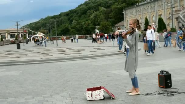 Kiev, Ukraine, June 2019: - Busker perform music on violin in square outdoor. Beautiful girl performing classical music on city street.